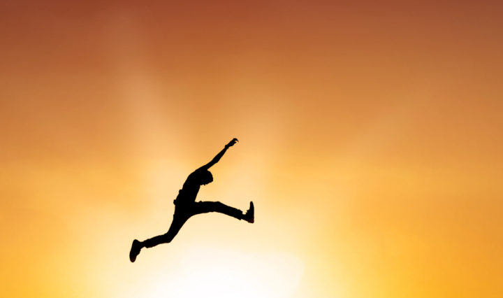 Silhouette of a man leaping against the background of an orange and yellow sunset