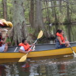 Students pushing off from the shore in their canoe