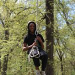 A student smiles as he zip lines through the ropes course