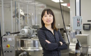 Angela Zeng stands in front of her beverage manufacturing equipment