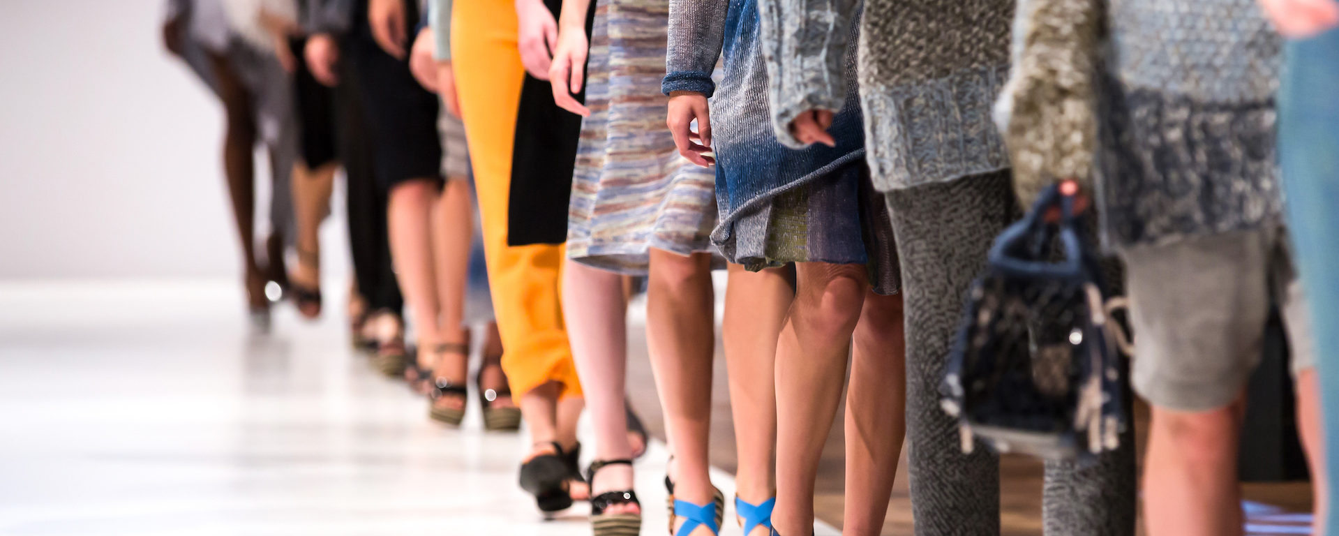 A line of models shown from the waist down wearing interesting, colorful fabrics and shoes