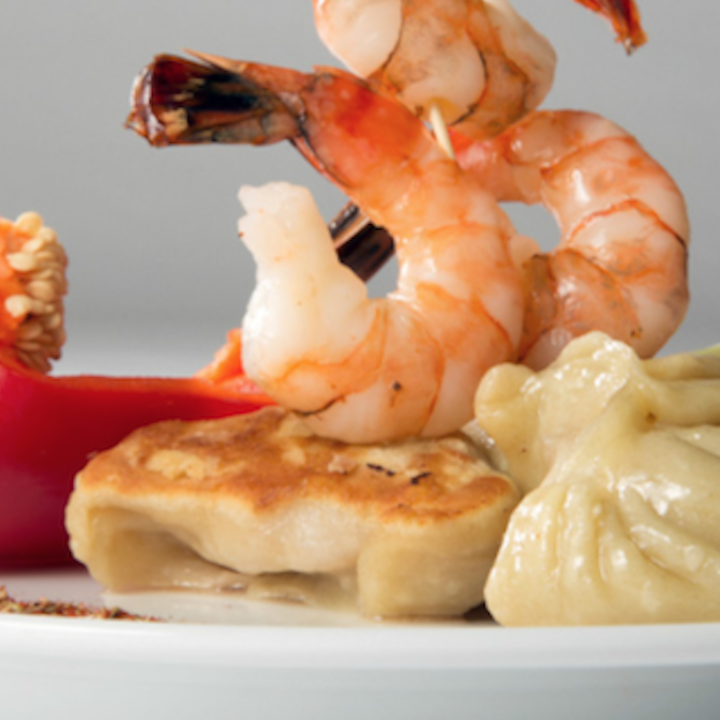 Asian dumplings topped with shrimp beautifully presented on a white plate