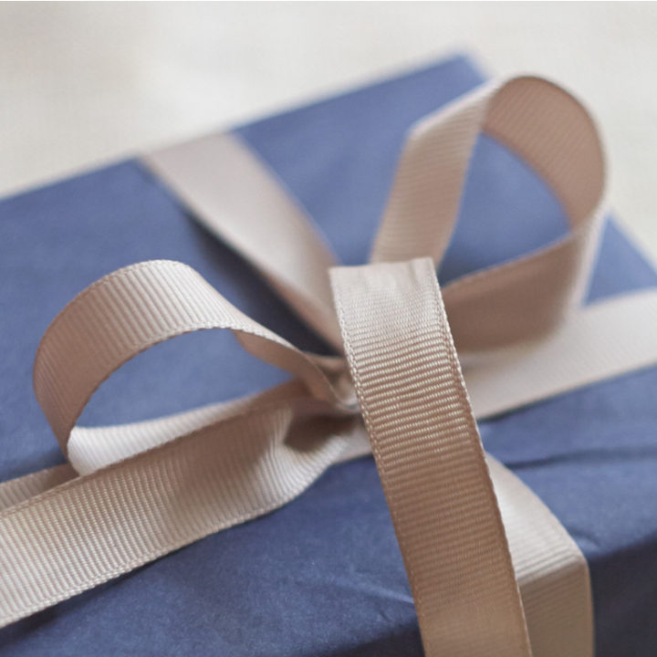 Gift wrapped in blue paper with a beige ribbon