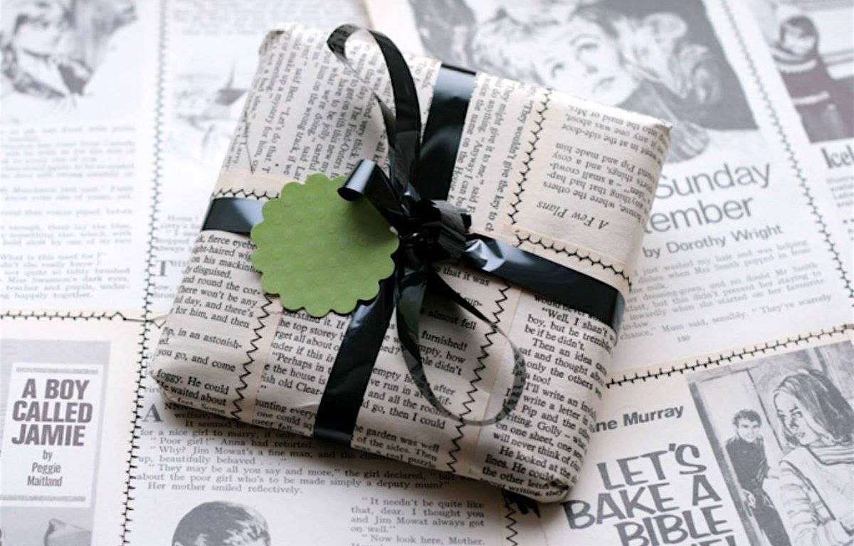sustainably wrapped gift on a newsprint-covered surface