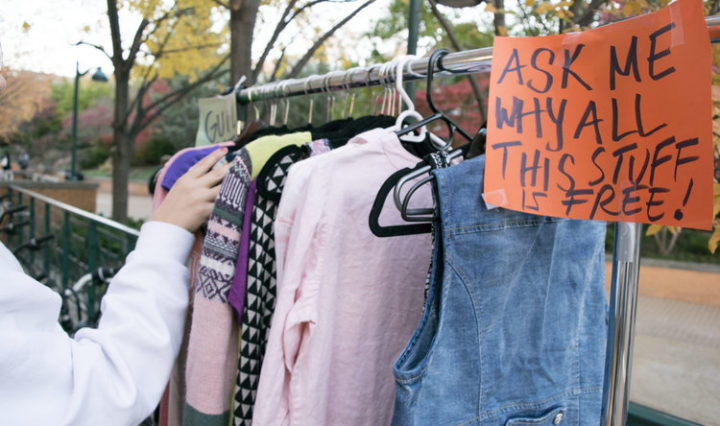 "A rack of clothing has a sign that reads ""Ask me why all this stuff is free."""