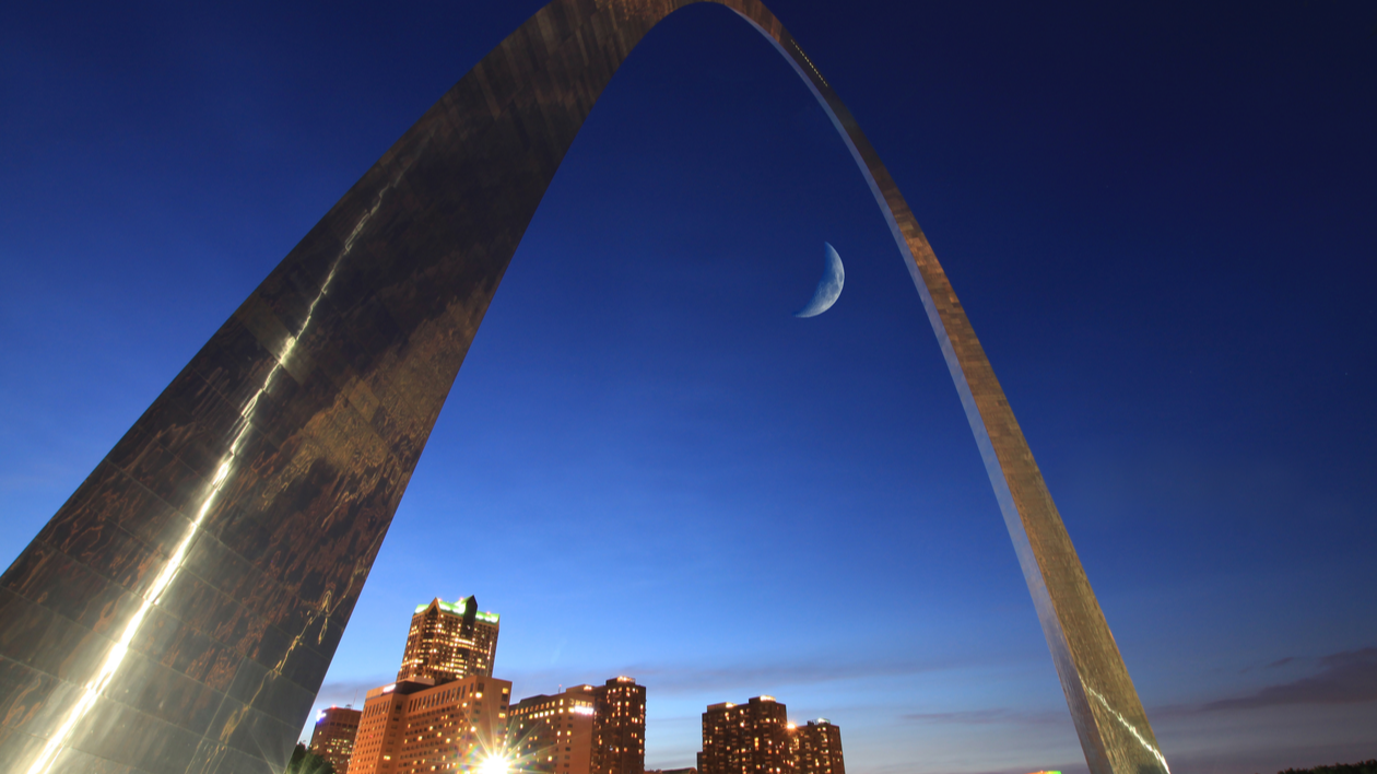 The St. Louis Gateway Arch at night against a dark blue sky with the moon behind it