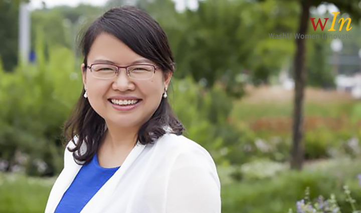 Asian woman in glasses and white lab coat smiles against a park-like backdrop