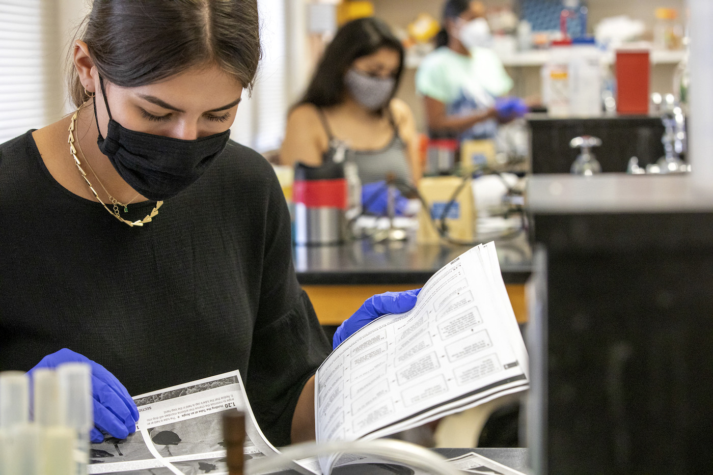 A female college student wearing a face mask and gloves in the lab