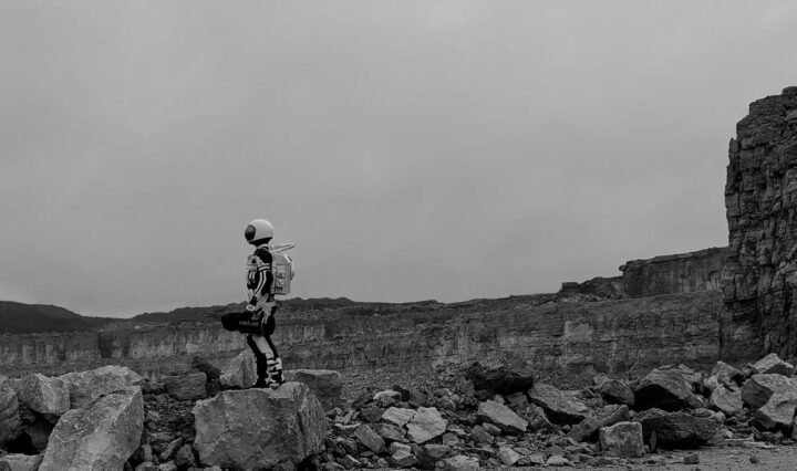 In a black and white photo, a persn wearing a spacesuit and carrying a scientific instrument explores a rocky terrain