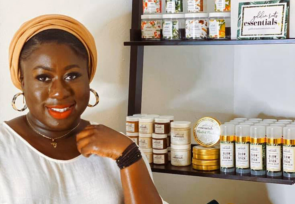 Golden Roots Essentials founder Fanta Kaba stands in front of shelves filled with beauty products